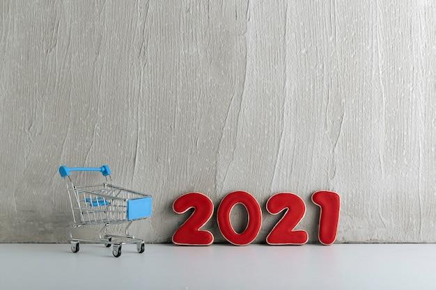 Piccolo carrello e numeri 2021 su sfondo chiaro. shopping per il nuovo anno. sconti di capodanno.