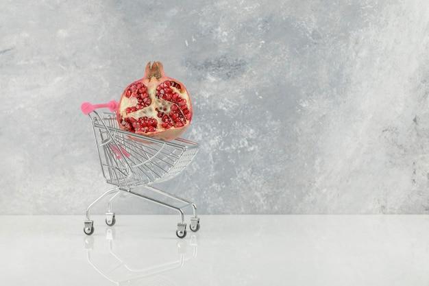 Piccolo carrello con melograni rossi freschi sul tavolo bianco.