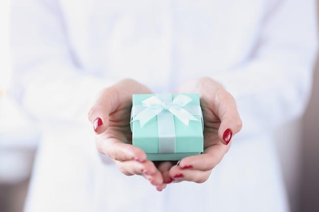 Piccola confezione regalo turchese in mani femminili. concetto di confezione regalo fai da te