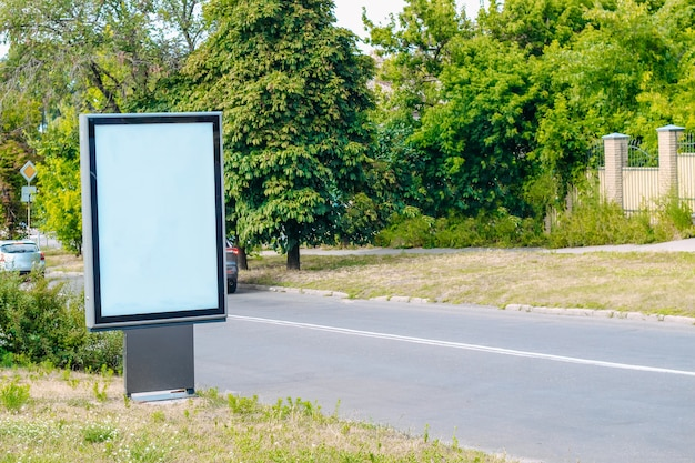 Piccolo cartellone verticale sulla strada in una piccola città verde