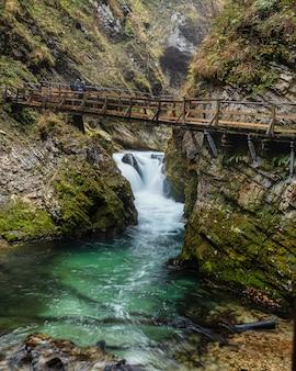 Piccola cascata e acque color smeraldo della gola di vintgar con via sopraelevata in legno con vista, slovenia