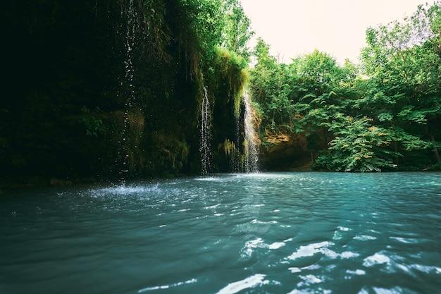 Una piccola cascata e un lago circondato da alberi in estate. meraviglioso paesaggio alla foce del fiume.