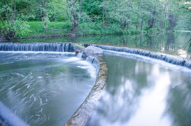 Piccola cascata su un piccolo ruscello pittoresco nella foresta