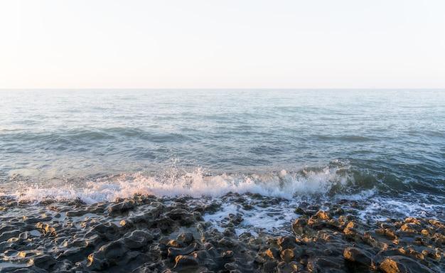 Piccole onde su una spiaggia rocciosa nel tempo nebbioso