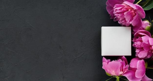 Piccola scatola bianca in una cornice di delicate peonie rosa su un bellissimo sfondo di cemento nero. concetto romantico. piatto lay.postcard.place per il testo.