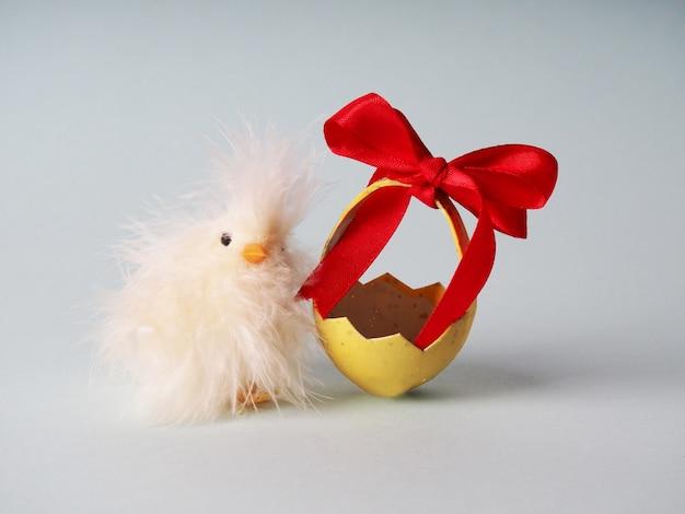 Piccolo pollo bianco accanto alle uova colorate per pasqua.