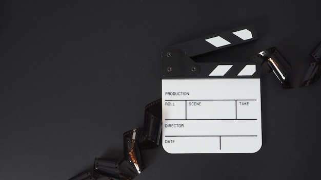 Piccolo ciak bianco e rotolo di pellicola su sfondo nero. utilizza nel settore della produzione di film e video.