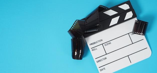 Piccolo ciak bianco e rotolo di pellicola su sfondo blu o turchese. viene utilizzato nella produzione di film e video.