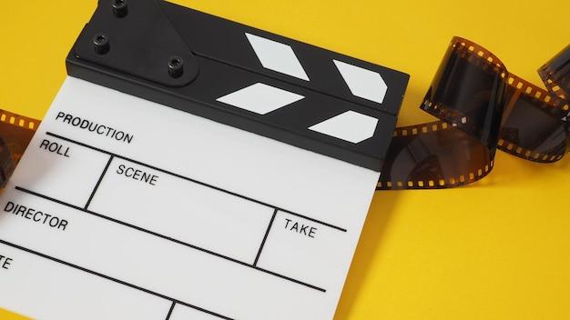Piccolo ciak bianco e rotolo di pellicola su sfondo giallo. viene utilizzato nella produzione di film e video.
