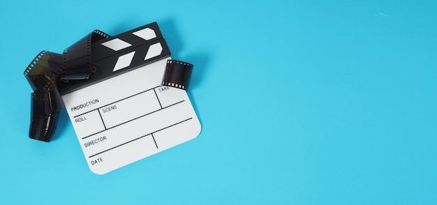 Piccolo ciak bianco o ardesia di film e rotolo di pellicola su sfondo blu o turchese. viene utilizzato nella produzione di film e video.
