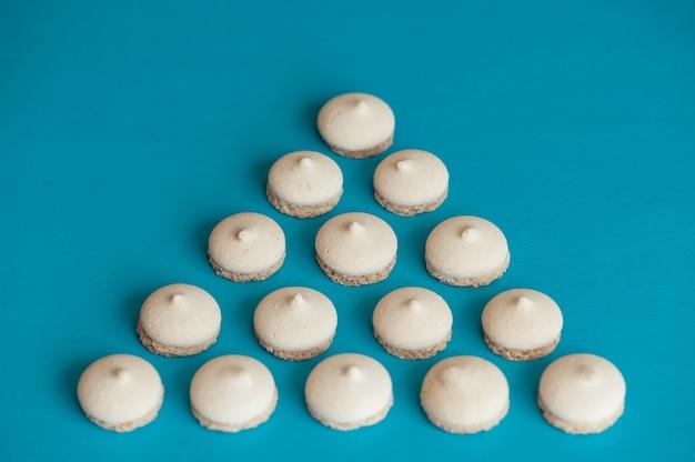 Piccoli biscotti bianchi sono disposti sotto forma di un triangolo su sfondo blu. fotografia concettuale del cibo.