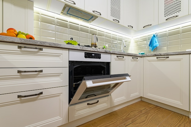 Piccola cucina bianca classica accogliente e confortevole, la porta del forno elettrico è aperta