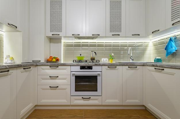 Interiore della cucina classica contemporanea bianca piccola accogliente e confortevole con mobili in legno