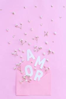 Piccoli fiori bianchi, busta rosa chiaro e parola amor su sfondo rosa chiaro vista dall'alto