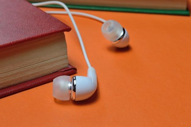 Piccole cuffie bianche e una pila di libri su uno sfondo arancione.