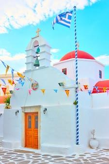 Piccola chiesa ortodossa bianca con bandiera greca nella città di mykonos, grecia