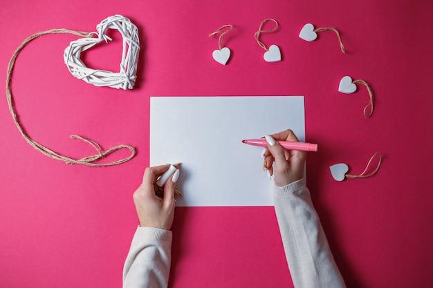 Piccoli cuori di legno bianchi e grande cuore di legno di vimini bianco con la corda su fondo rosa con lo spazio della copia. la carta di san valentino con la donna passa la scrittura con la penna rosa sul foglio di carta bianco.