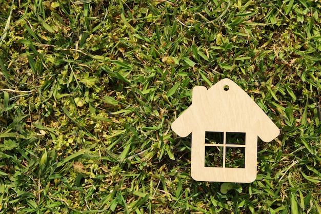 Piccola casa di legno su erba verde. acquistare una proprietà