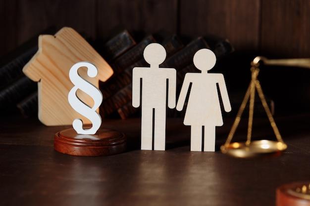 Piccola casa in legno con figure familiari e un segno di paragrafo come concetto di assicurazione