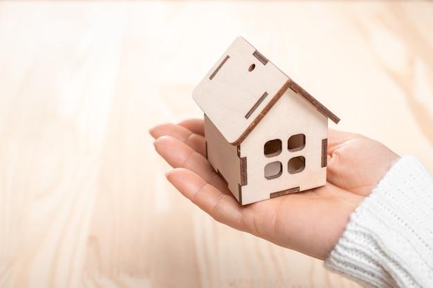Piccola casa in legno in mano di una donna su legno