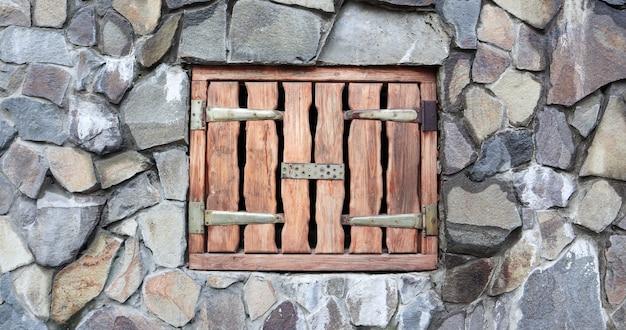Piccola porta di caricamento in legno nel muro del vecchio fienile in pietra. antico muro di pietra con piccola porta in legno forte. piccola porta d'ingresso in legno antico in miniatura in una parete gigante di grandi pietre grigie.