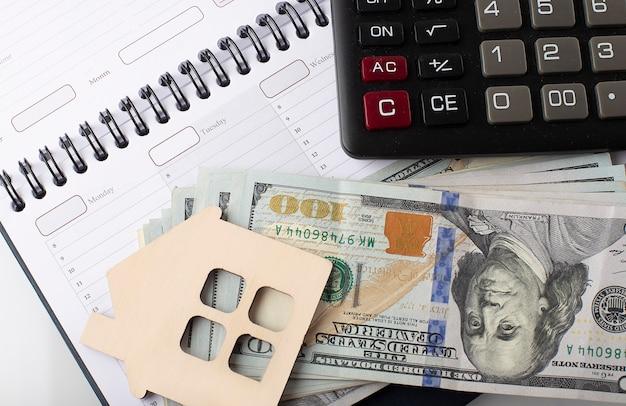 Piccola casa modello in legno sullo sfondo delle banconote in dollari usa sulla pianificazione