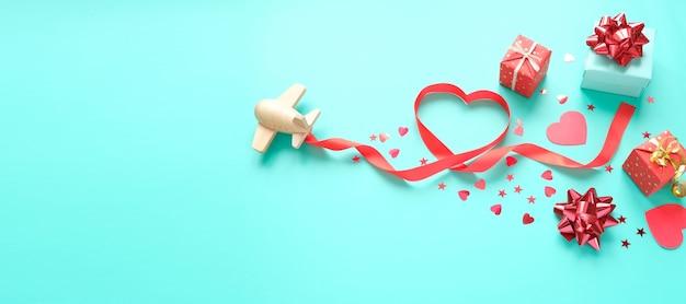 Un piccolo aeroplano giocattolo di legno trasporta gli elementi di san valentino. vapore scia di paillettes a forma di cuore, regali, fiocco e glitter rossi. san valentino