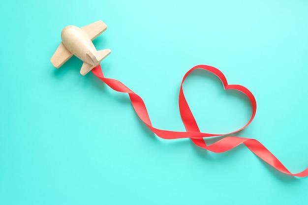Un piccolo aeroplano giocattolo di legno trasporta gli elementi di san valentino. scia di vapore di paillettes a forma di cuore e nastro rosso a forma di cuore. san valentino