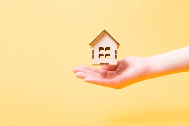 Piccola casa di legno del giocattolo sulla mano di una donna