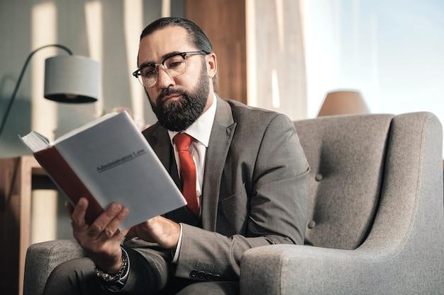 Difensore intelligente. avvocato barbuto intelligente che indossa cravatta rossa e costume grigio che legge il diritto amministrativo
