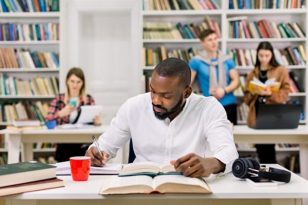 Giovane studente afroamericano attento astuto nell'abbigliamento casual che studia nella biblioteca universitaria e che prende le note
