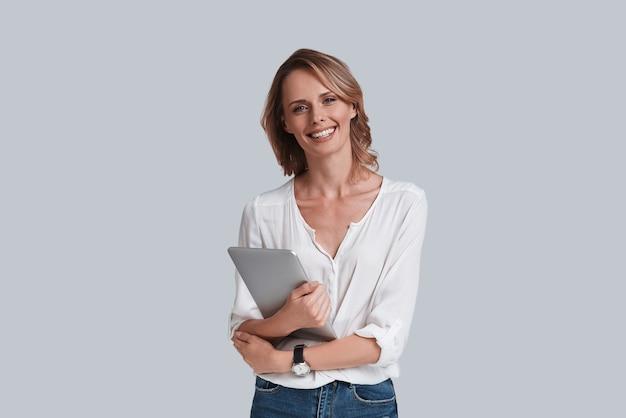 Intelligente e bella. attraente giovane donna che guarda la telecamera e sorride mentre si trova su uno sfondo grigio gray