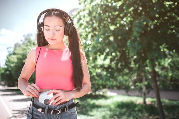Una ragazza intelligente e bella a cui piace ascoltare la musica sta guardando il giocatore. sta collegando le cuffie al lettore bianco. la ragazza è in piedi sulla strada.