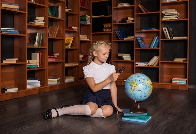 Una ragazza bionda intelligente in uniforme scolastica si siede e studia un mappamondo in biblioteca