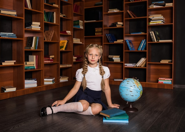 Una ragazza bionda intelligente in uniforme scolastica si siede con un globo e libri in classe