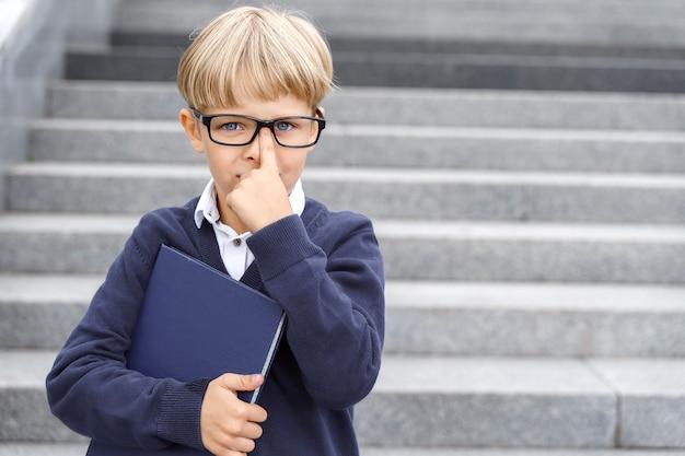 Studente ragazzo intelligente con gli occhiali con una cartella blu si leva in piedi sui gradini e si aggiusta gli occhiali