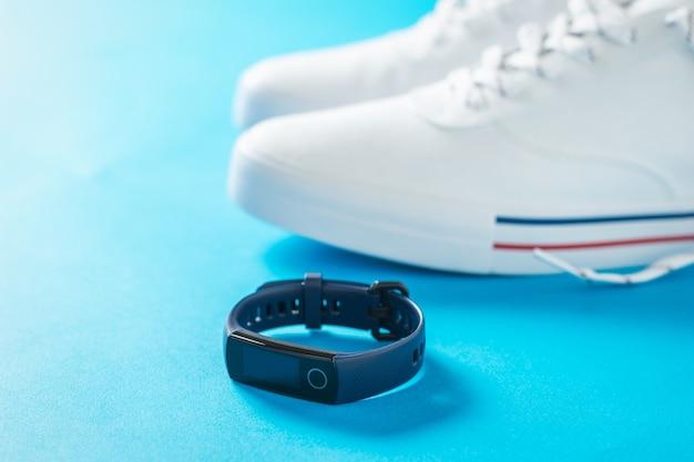 Braccialetto intelligente su uno sfondo di scarpe da ginnastica bianche sul blu
