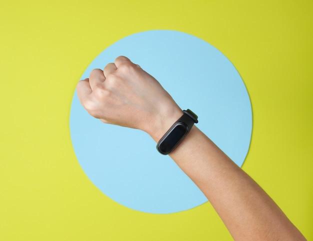 Braccialetto intelligente sul polso della mano su verde con cerchio blu