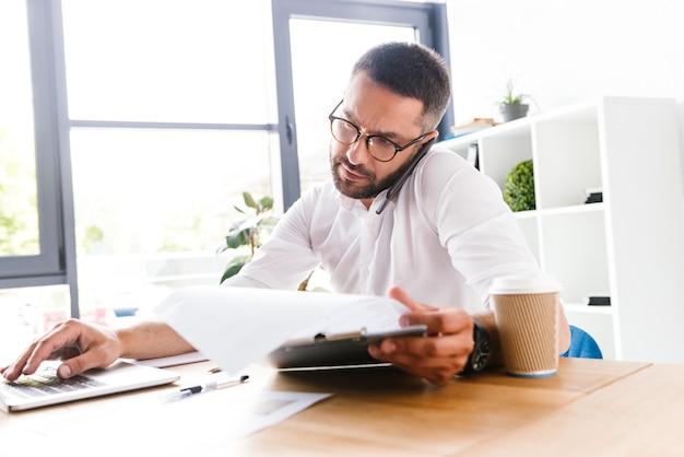 Smart business man 30s in camicia bianca verificando le informazioni da documenti cartacei utilizzando laptop e parlando al cellulare, durante il lavoro in ufficio