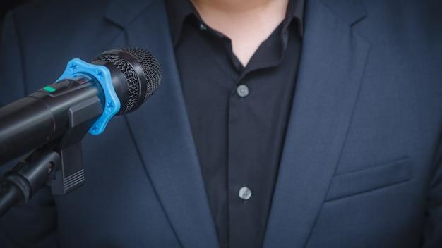 Discorso di uomo d'affari intelligente e parlando con microfoni in sala seminari o sala conferenze parlante