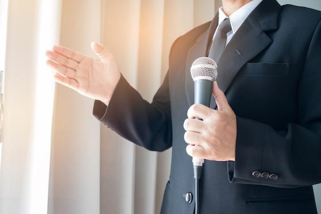 Discorso intelligente uomo d'affari e parlando con microfoni
