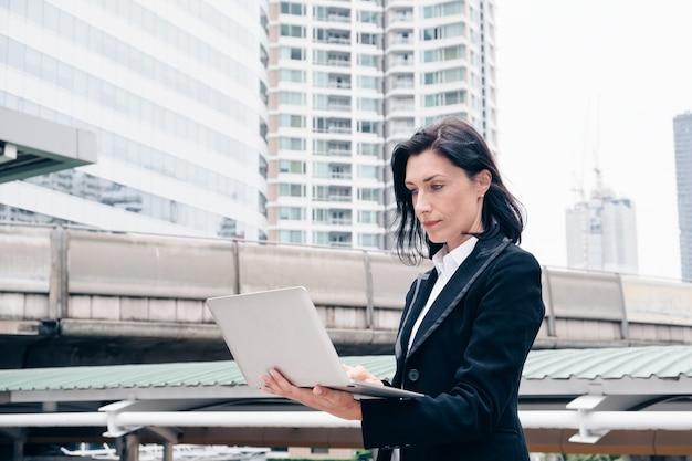Una donna d'affari intelligente sta usando il laptop in città
