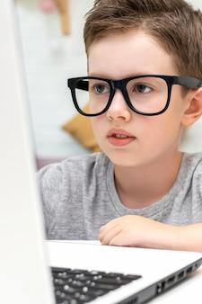 Un ragazzo caucasico intelligente con gli occhiali guarda lo schermo del laptop e impara a programmare