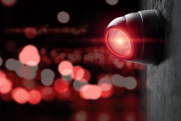 Telecamera cctv intelligente sul muro con luci rosse.