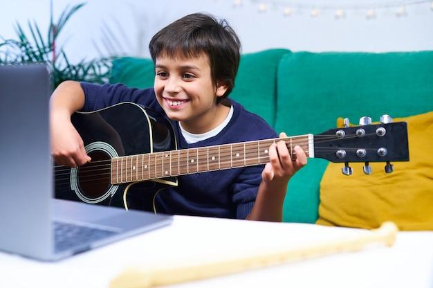 Bambino intelligente e allegro che impara a suonare la chitarra con lezioni online su laptop seduto sul divano di casa.