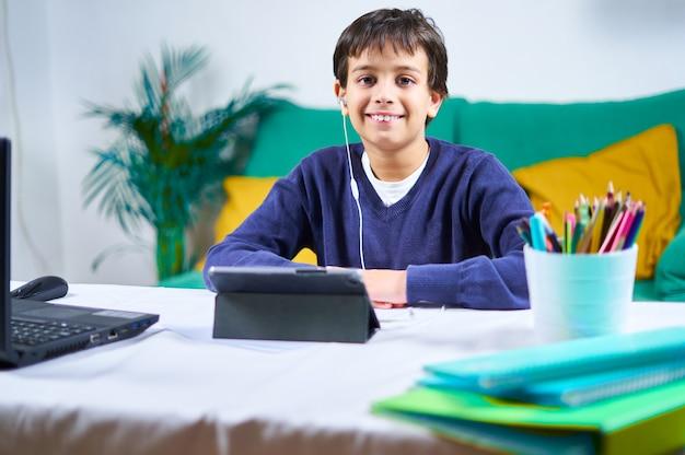 Bambino intelligente e allegro che guarda la telecamera durante le lezioni online con tablet e laptop seduto sul divano di casa.