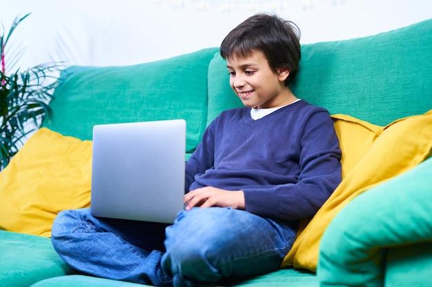Bambino intelligente e allegro che fa una videoconferenza con il laptop seduto sul divano di casa