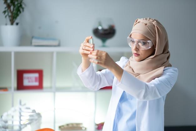 Chimico intelligente. chimico femminile intelligente che indossa occhiali protettivi e provetta con hijab