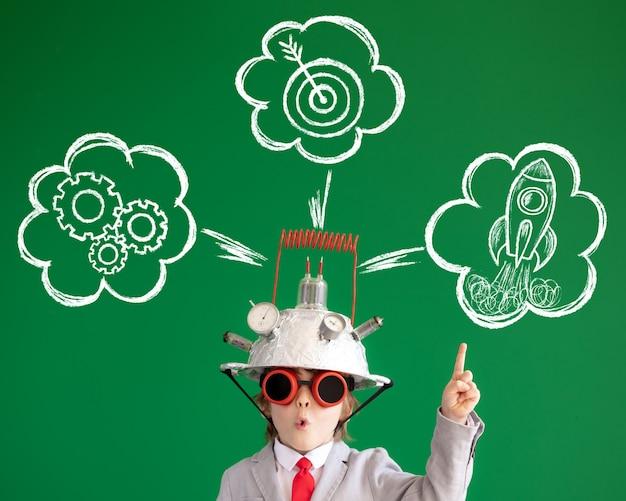 Bambino intelligente contro la lavagna verde bambino divertente che indossa il casco con lampadina