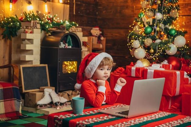 Bambino intelligente con la faccia allegra che acquista regali ai genitori calzino di natale sogni di bambino di natale comp...